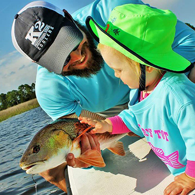 A fisherman and a young child hlding a fresh caught redfish in the Tallahassee bay system