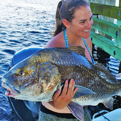 A female fisherman holding a huge black drum caught off the coast of Tallahassee