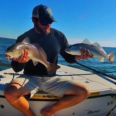 The charter captain holding two fresh caught redfish harvested from Tallahassee coastal waters